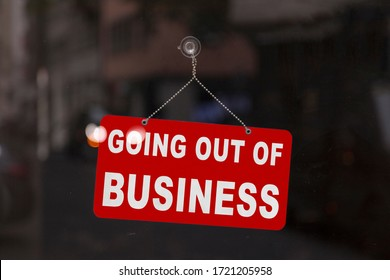 "Close-up on a red closed sign in the window of a shop displaying the message ""Going out of business""."