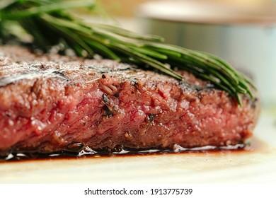 Closeup on roasted beef medium rare steak with a rosemary