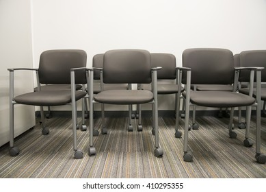 Closeup on row of empty chairs at the reception waiting area of an interior office building.