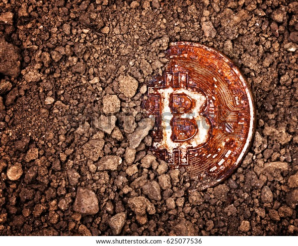 closeup on rusty bitcoin buried in a ground obsolescence concept