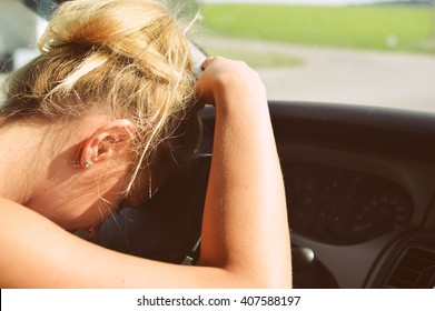 Closeup on sad tired beautiful lady driver leaning on the wheel of a car on green outdoors background