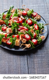 Close-up on salad on a skewers: of roasted chicken breast with paprika, piquante peppers stuffed with cream cheese,  and spinach on skewers on a black plate on a dark wooden table, vertical view