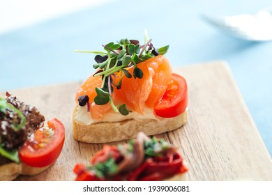 Closeup on salmon and tomato bruschetta with herbs on a wooden board