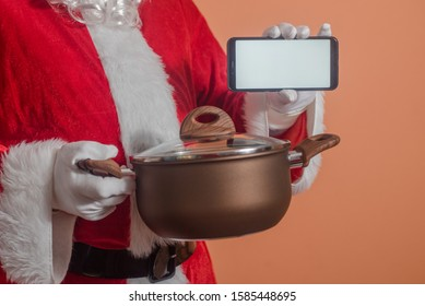 Closeup on Santa Claus showing mobile phone and holding in hand preparing cooking pan working in kitchen for food delivering. Mock up copy space modern display photography background