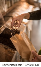 close-up on the seller's hands filling an organic coffee bag from a bulk dispenser