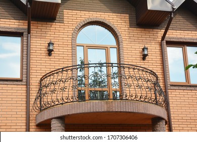 A close-up on semi-circled balcony with wrought iron railings, arched glass door and roof gutter system with downpipes of a brick house.