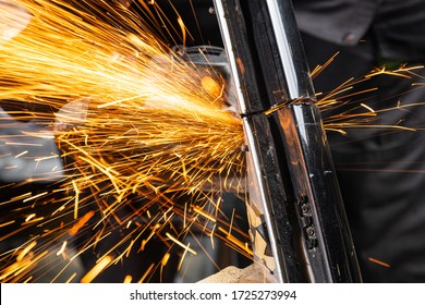 Close-up on the sides fly bright sparks from the angle grinder machine. A young male welder  grinds a metal product with angle grinder in the garage