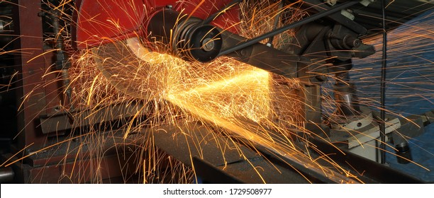 Close-up on the sides fly bright sparks from the angle grinder machine,Metal sawing. Hot sparks at grinding steel material.