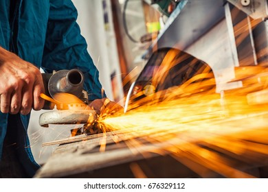 Close-up on the sides fly bright sparks from the welding machine. A young male welder in a blue working overall and working gloves grinds a metal product with angle grinder in the garage