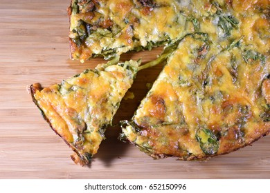 Close-up on a sliced crustless spinach quiche on a wooden board