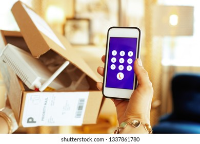 Closeup on smartphone in hand of modern housewife trying to return problematic or unsuitable smart home device in the living room.