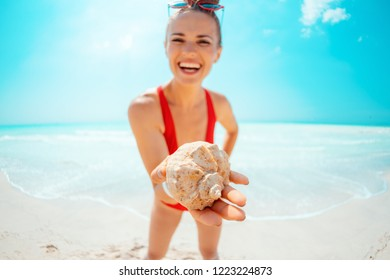 Closeup on smiling young woman in red swimwear on the seacoast showing a sea shell