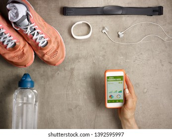 Closeup on sneakers, heart rate monitor, bottle of water, white fitness tracker, headphones laying on the floor and female hand holding smartphone with sports training data