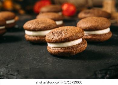 Closeup on sponge cocoa cookies whoopie pies on the black background, horizontal