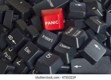 Closeup on a stack of black computer keyboard keys with red panic button