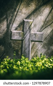 Closeup on a stone cross on a tomb in a cemetery