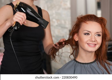 closeup on stylist hands drying redhead woman hair in salon. Young female giving new hair style to woman at parlor