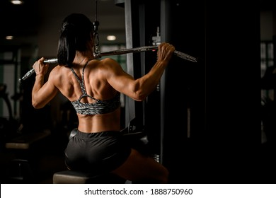 Close-up on tense back muscles of woman bodybuilder who pulls on sports simulator in the gym.