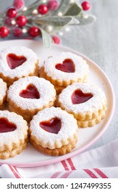 Close-up on traditional Christmas Linzer cookies filled with strawberry jam on light table with Xmas decorations