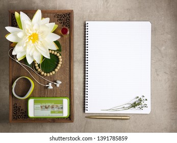 Closeup on tray with fragrant stuff for aroma yoga, beads, fitness tracker, headphones and smartphone with personal yoga trainer app and opened notebook with pen laying on the floor.