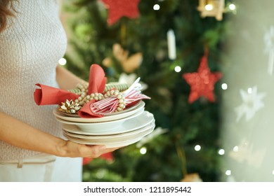 Closeup on trendy woman with serving plates near Christmas tree