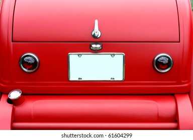 closeup on trunk of a red antique car and license plate