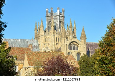 Close-up on turrets, spires and the Octagon of the Cathedral of Ely in Cambridgeshire, Norfolk, UK, with medieval roofs in the foreground and Autumn colors