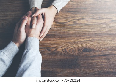 Closeup on two young lovers holding hands at a table