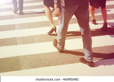 close-up on unidentified people legs crossing street in vintage style