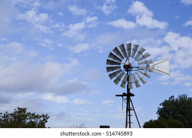 Closeup on upper portion of Vintage Wind Mill in Central California against partly cloudy sky