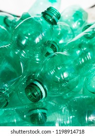 Close-up on used and empty green plastic water bottles