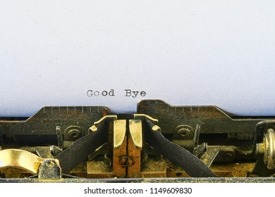 Closeup on vintage typewriter. Front focus on letters making Good Bye text. concept image with retro office tool.