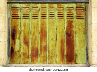 Close-up on weathered, rusty exterior metal blind, pained in green. Old texture background.