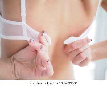 close-up on woman back with a hand try to take her bra off by unhooking the clasp of her bra