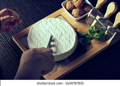 Closeup on woman cutting fresh cheese.