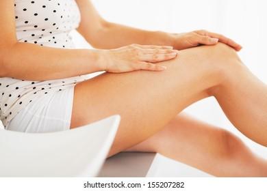 Closeup on woman examining leg in bathroom