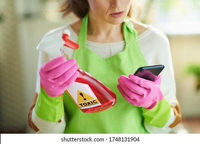 Closeup on woman in green apron and pink rubber gloves in the living room in sunny day reading about cleaning product on Internet using smartphone.