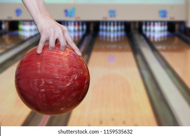Close-up on woman hand holding bowling ball against bowling alley