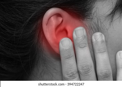 close-up on woman hand touch her ear with pain