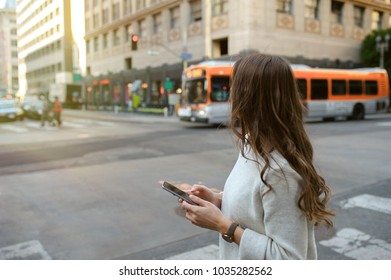 Close-up on woman hands holding smartphone on boulevard in urban scenery, downtown.