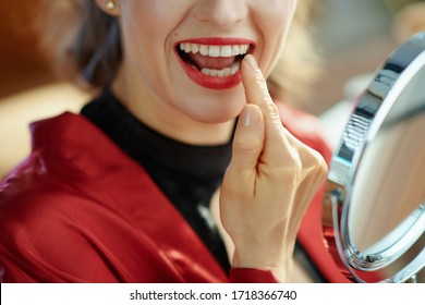 Closeup on woman in the living room in sunny day looking in mirror and checking teeth.