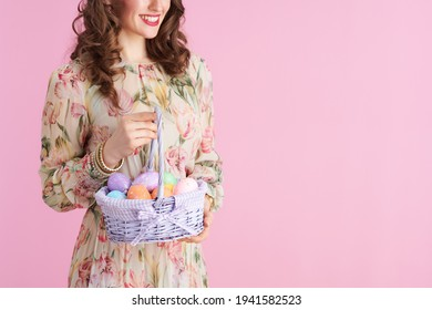 Closeup on woman with long wavy brunette hair with basket of easter eggs isolated on pink.