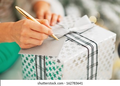 Closeup on woman signing card on christmas present box