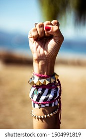 Closeup on woman's hand raise fist in the air wearing red nail polish, rings, bracelets, she is determined and it's on a beach by a summer sunny day, colorful image retro style
