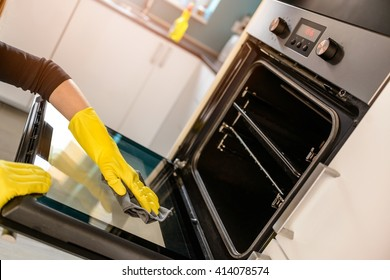 Closeup on woman's hands in yellow protective rubber gloves cleaning oven with rag