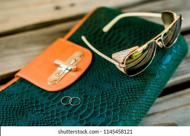 Close-up on a wooden background a green snake-skin bag with orange clasps, a sunglasses and two silver rings. Modern fashion concept and everyday women's clothing or accessories.