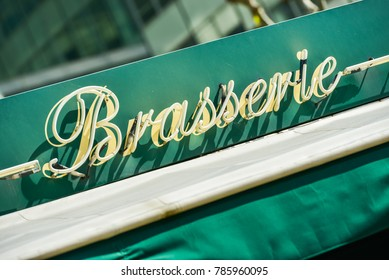 "closeup on the word brewery (""Brasserie"" in french) on an green arbor"