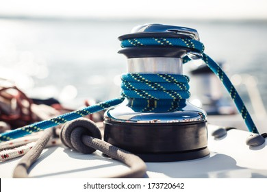 Closeup on yacht cord crank, rope holder on white sail background