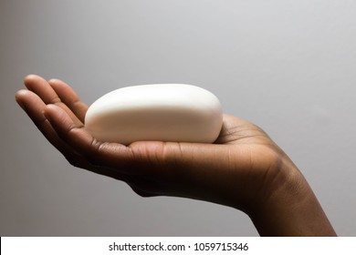 Closeup on young African American woman hands with soap bar isolated  on white background for Hygiene. Cleaning Hands. Washing hands with soap. Closeup on young woman hands with soap bar