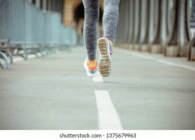 Closeup on young sports woman in sport clothes on Pont de Bir-Hakeim bridge in Paris jogging.